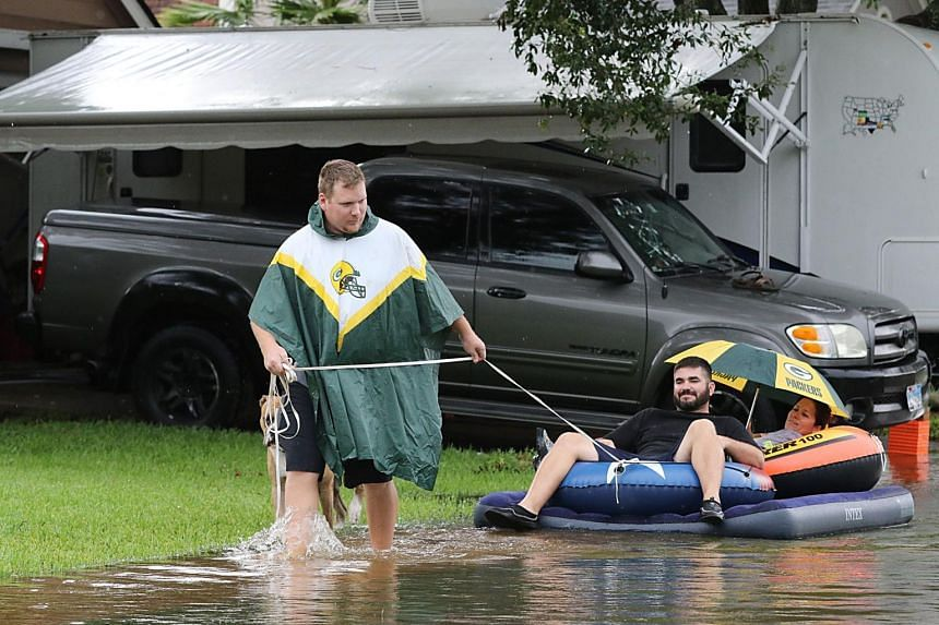 A man pulls his friends on a raft on flooded Apple Street in Pearland as the US fourth city city battles with tropical storm Harvey and resulting floods, on Aug 27, 2017.