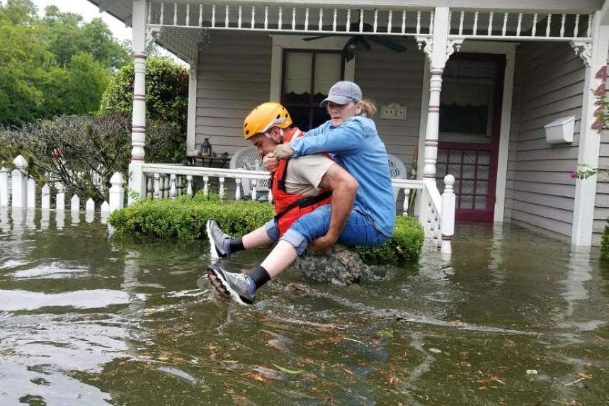 A Texas National Guard soldier carries a woman on his back in Houston on Aug 27, 2017.