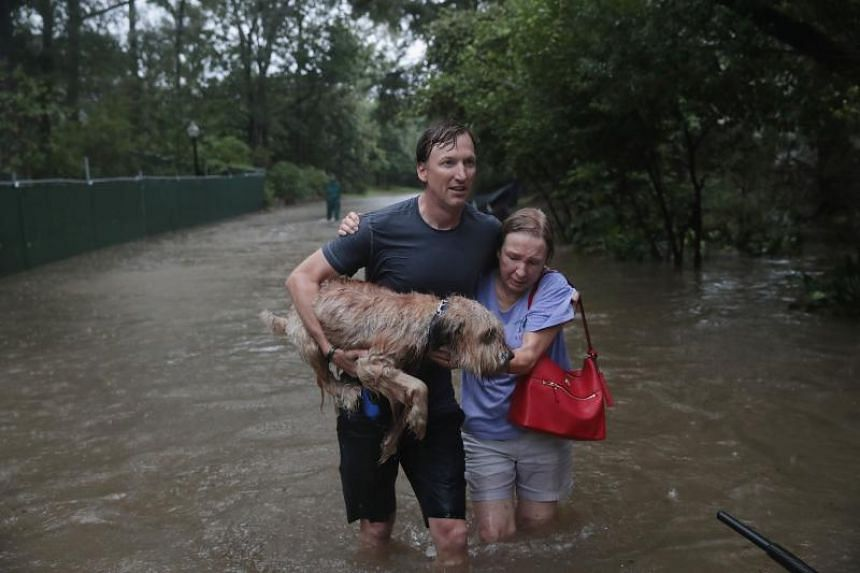 Andrew White (left) helps a neighbour down a street after rescuing her from her home in his boat in the upscale River Oaks neighborhood in Houston on Aug 27, 2017.