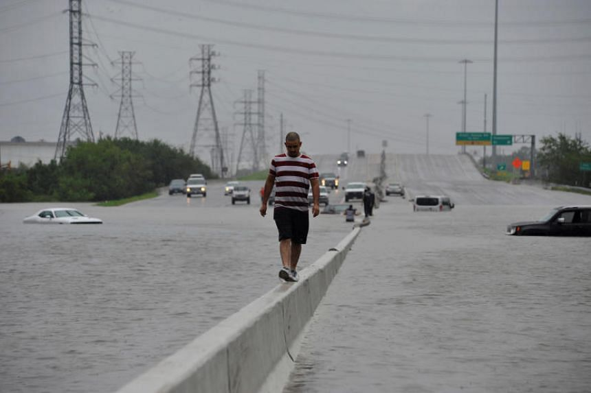 A stranded motorist escapes floodwaters on Interstate 225 after Hurricane Harvey inundated the Texas Gulf coast with rain causing mass flooding in Houston, Texas, on Aug 27, 2017.
