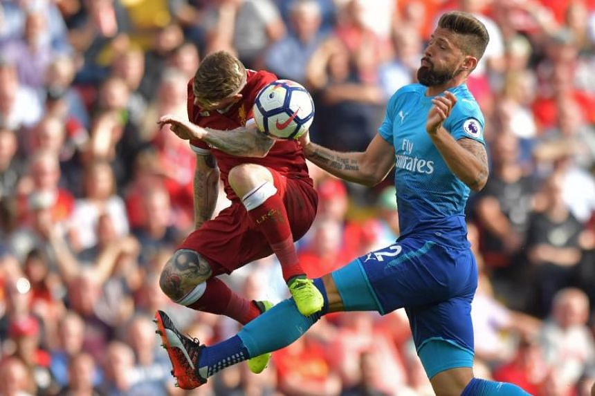 Liverpool's Spanish defender Alberto Moreno (left) vies with Arsenal's French striker Olivier Giroud at Anfield on Aug 27, 2017. /