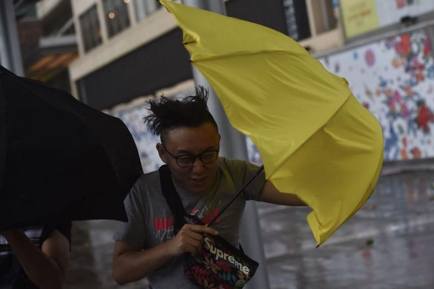 Pedestrians struggle with their umbrellas during strong winds and rain brought on by severe tropical storm Pakhar in Hong Kong on Aug 27, 2017.