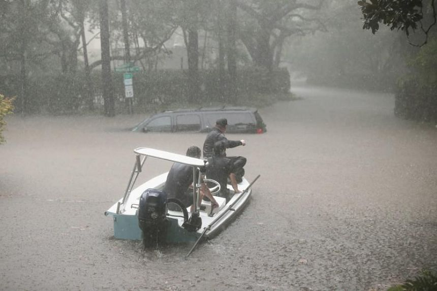 Volunteers and officers help to rescue residents in Houston's upscale River Oaks neighbourhood.