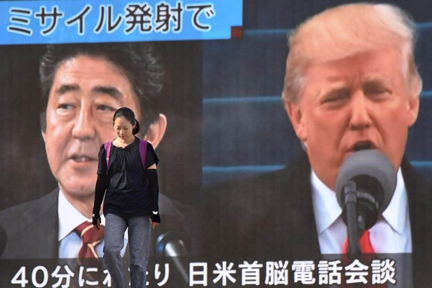 A woman walks in front of a huge screen displaying Japanese Prime Minister Shinzo Abe (left) and US President Donald Trump (right) in Tokyo on Aug 29, 2017, following a North Korean missile test that passed over Japan.