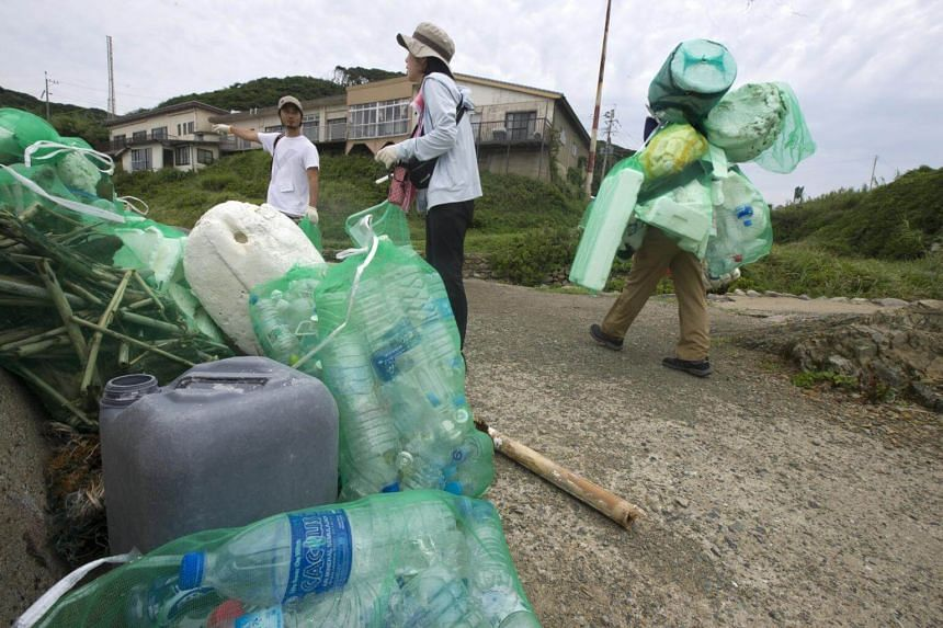 Volunteers clean up plastic from a beach on Oshima island, Japan, on Aug 26, 2017.