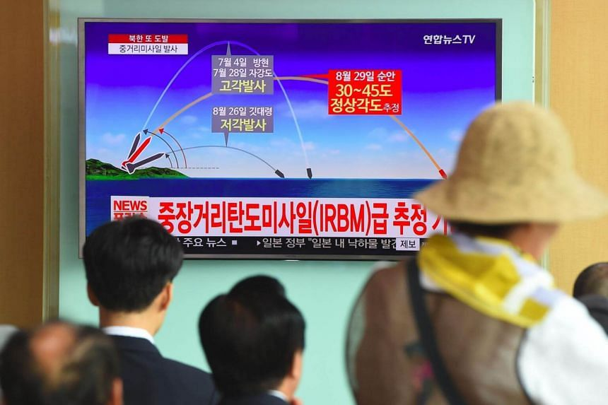 People watch a television news screen showing a graphic of a North Korean missile launch, at a railway station in Seoul, on Aug 29, 2017.
