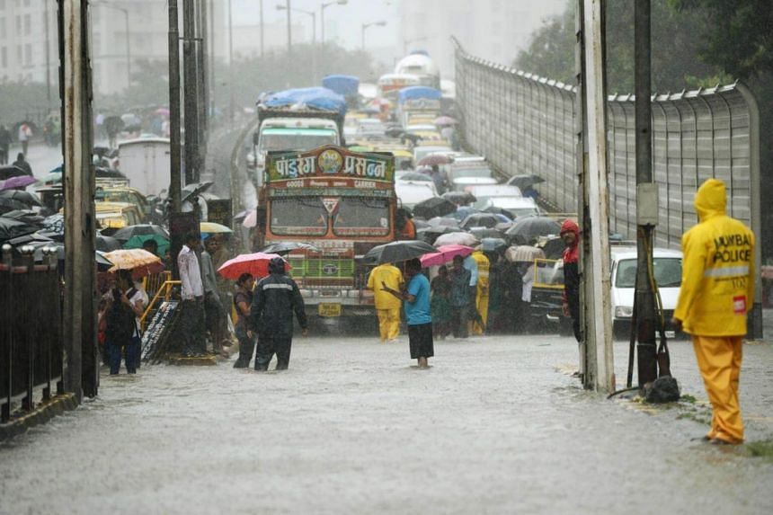 People wade next to vehicles during a traffic jam along a flooded road during heavy rain showers in Mumbai on Aug 29, 2017.