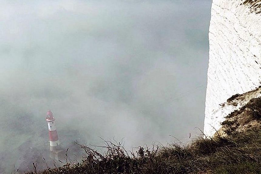 """A """"mist"""" surrounding Beachy Head Lighthouse along the southern English coast, near Eastbourne, seen on Sunday in this picture obtained from social media. Emergency services evacuated a beach in Sussex after people reported pain and a stinging feeling"""