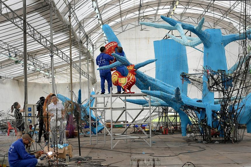 """Craftsmen from Sichuan hanging one of 112 animal lanterns that will adorn a """"family tree"""" which measures 12m high by 10m wide. This year's Mid-Autumn Festival celebrations will feature more than 1,000 lanterns and more than 10,000 LED light bulbs. Th"""