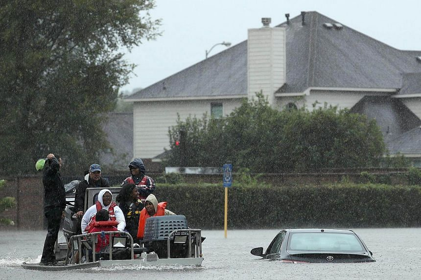 Residents are evacuated from their homes after severe flooding following Hurricane Harvey in the Cedarwood Creek subdivision in north Houston.