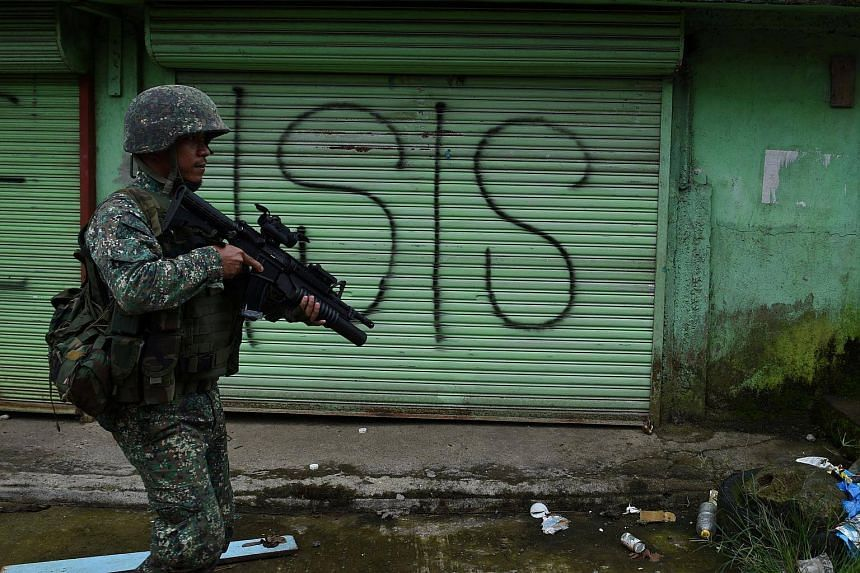 A Philippine Marine walks past graffiti during a patrol along a deserted street at the frontline in Marawi.