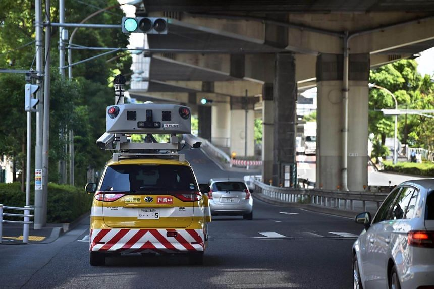 An Infra Doctor vehicle used by the Tokyo highway inspection system driving under a section of highway in Tokyo.