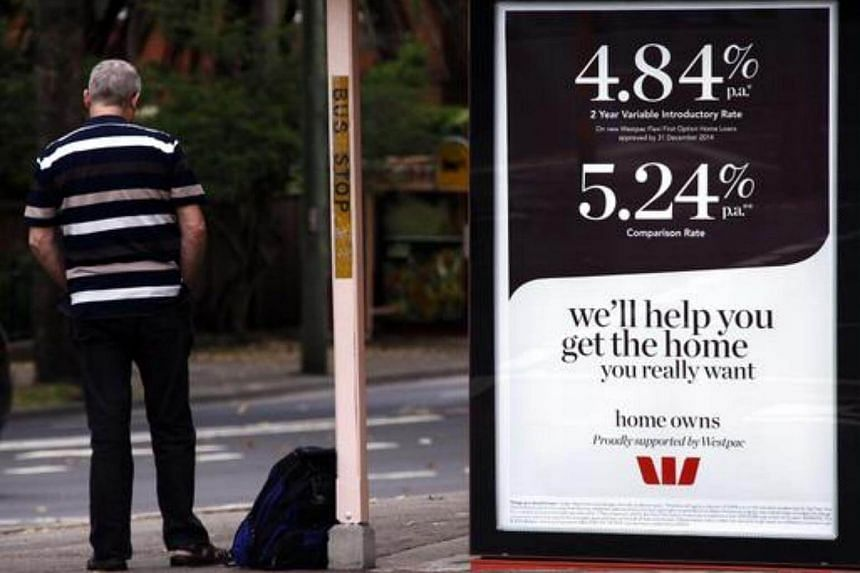 A man waits at a bus stop next to a sign advertising bank interest rates for home loans in Sydney on Oct 7, 2014.