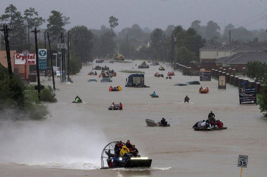 Residents use boats to evacuate flood waters from Tropical Storm Harvey along Tidwell Road east Houston, Texas, U.S. Aug 28, 2017.