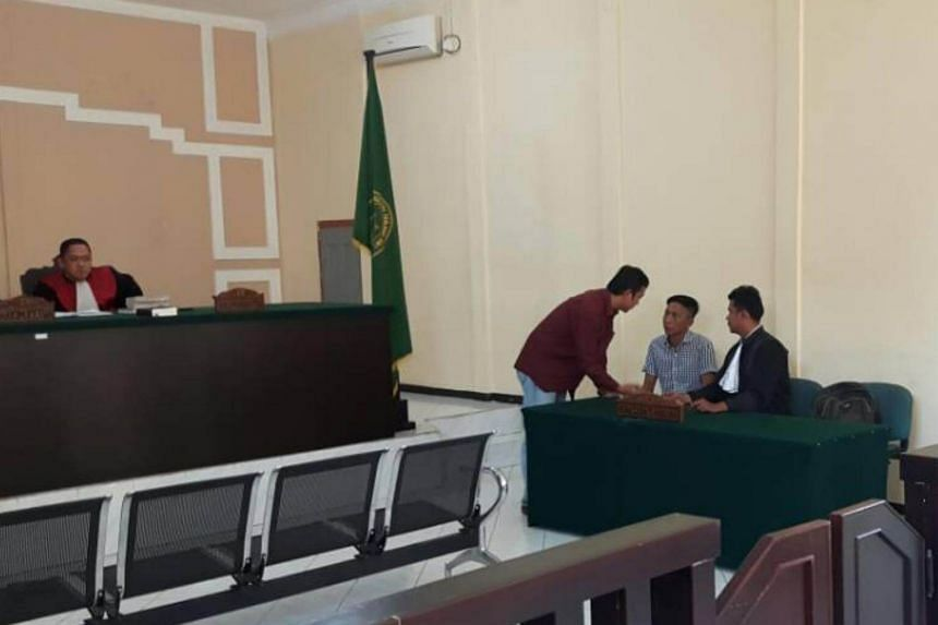 Singaporean Shoo Chiau Huat (wearing a black and white shirt) speaking to his interpreter and lawyer in court on May 3, 2017.  Indonesia's Tanjung Pinang district court on Wednesday (May 3) dismissed the charge against the boat captain for sailing in