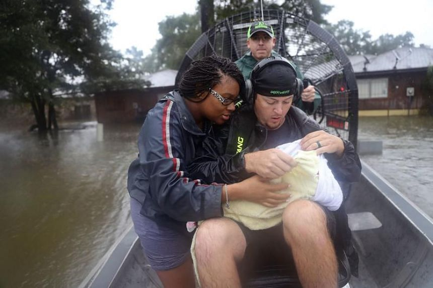 Shardea Harrison looks on at her 3 week old baby Sarai Harrison being held by Dean Mize as he and Jason Legnon used his airboat to rescue them from their home in Houston on Aug 28, 2017,