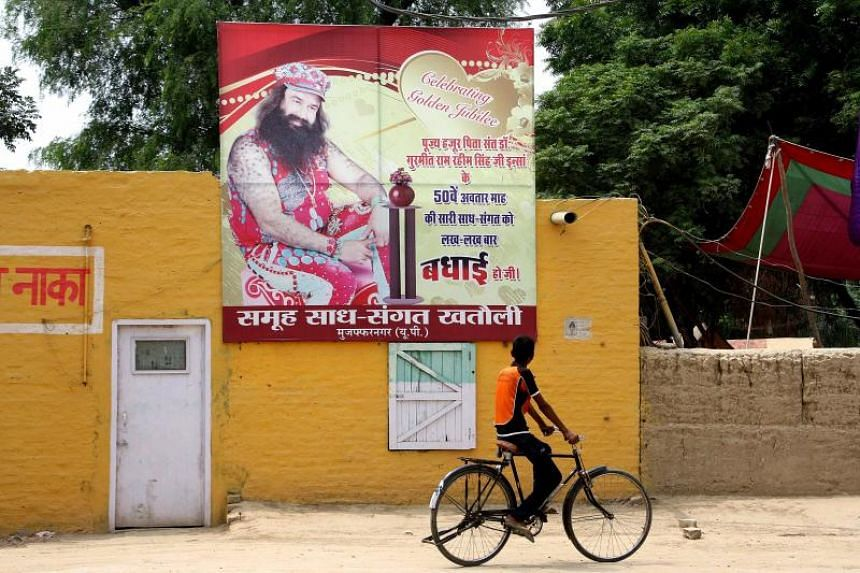 An Indian youth rides a bicycle past a poster of controversial guru Gurmeet Ram Rahim Singh in Sirsa on Aug 28, 2017.