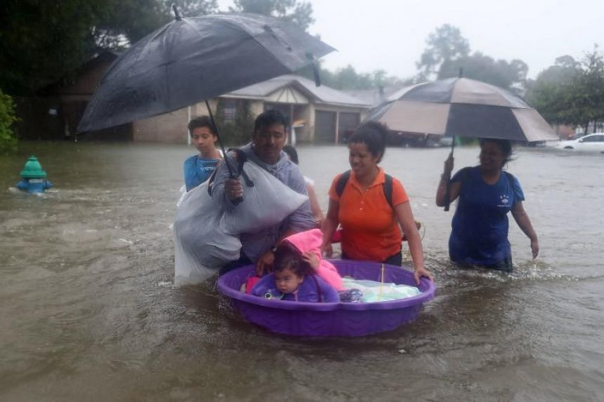 People walk down a flooded street as they evacuate their  flooded homes in Houston on Aug 28, 2017.