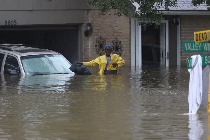 People wait to be rescued from their flooded homes in Houston on Aug 28, 2017.