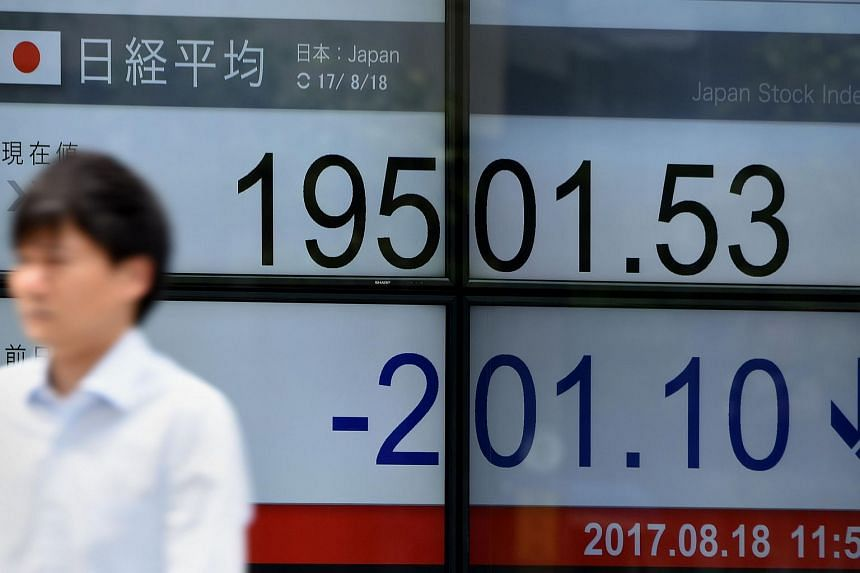A man walks past a stock quotation board flashing the Nikkei 225 key index of the Tokyo Stock Exchange in front of a securities company in Tokyo on Aug 18, 2017.