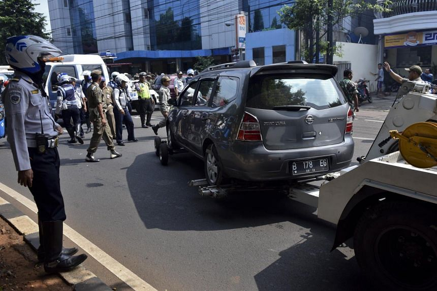 Jakarta Transportation Agency officers tow away a car that was parked on a sidewalk on Jl. Abdullah Syafei in Tebet, South Jakarta. PHOTO: THE JAKARTA POST/ASIA NEWS NETWORK