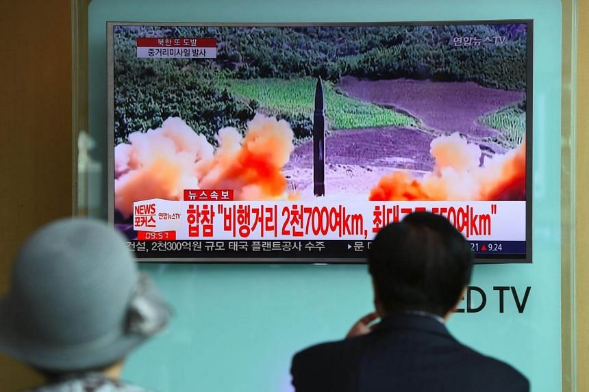 People watch a television news screen showing file footage of a North Korean missile launch, at a railway station in Seoul on Aug 29, 2017.