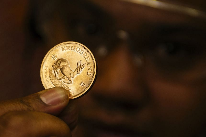 A worker holds up a proofed krugerrand gold coin in Germiston, South Africa.