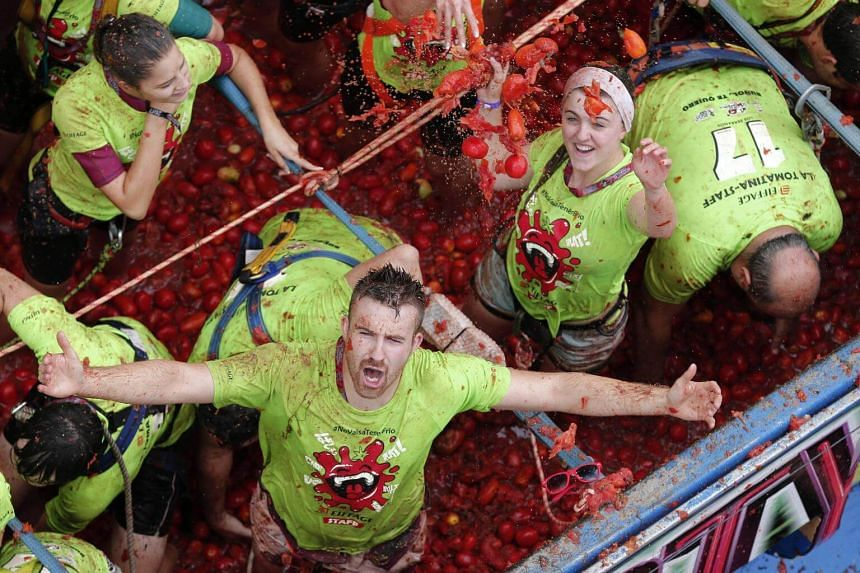 People take part in the traditional tomato fight called 'Tomatina' on board a truck full of tomatoes in Bunol, Spain, on Aug 30, 2017.