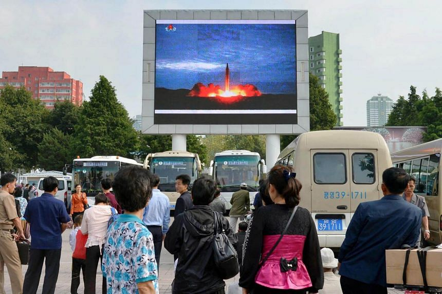 North Koreans watch a news report showing North Korea's Hwasong-12 intermediate-range ballistic missile launch on electronic screen at Pyongyang station in Pyongyang, North Korea, on Aug 30, 2017.