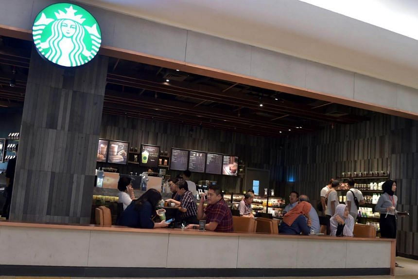 Customers sitting inside a Starbucks cafe at a shopping mall in Jakarta.