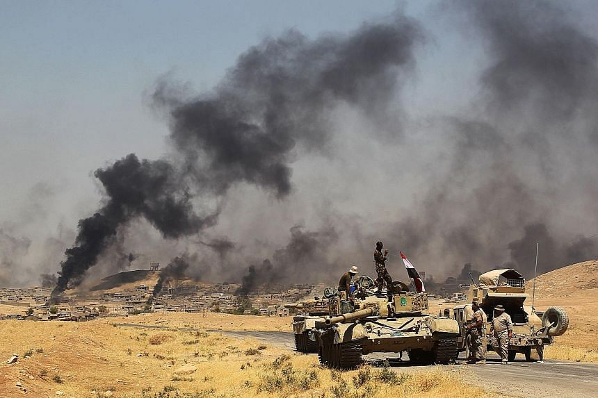 Smoke billowing from parts of the town of al-'Ayadiya, north of Tal Afar, as Iraqi forces advance during the ongoing operation to retake the area from ISIS on Monday.