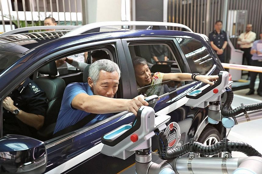 PM Lee Hsien Loong testing the prototype of the automated passenger-in-car clearance system at Woodlands Checkpoint.