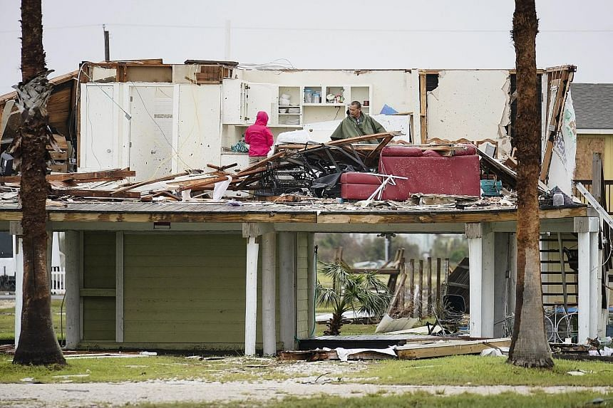 Rockport residents working to clean up their house in the aftermath of the storm on Monday. The floods could destroy up to $27 billion in insured property, analysts say. People being rescued from a flooded neighbourhood in Houston after it was inunda