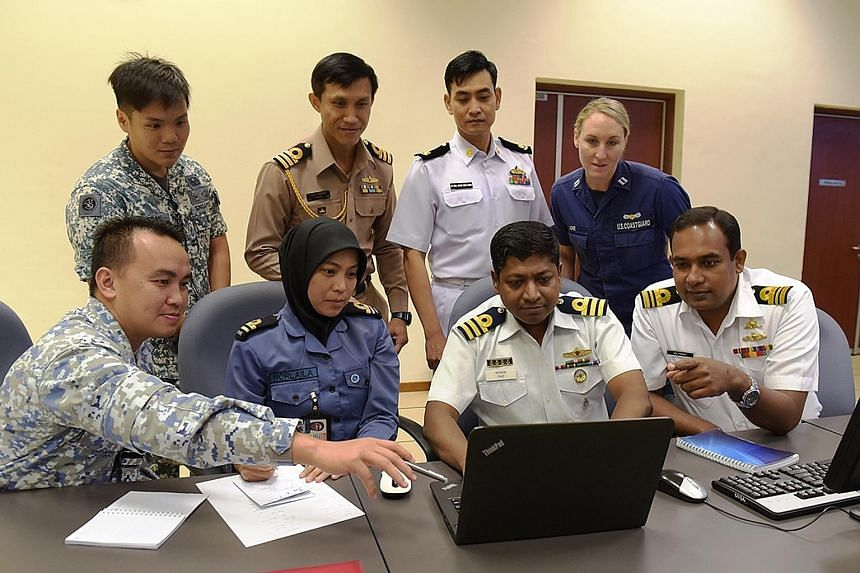 Seacat participants working together to share information and to coordinate responses to maritime threats. The Republic of Singapore Navy's Accompanying Sea Security Team conducting a compliant boarding during an exercise.