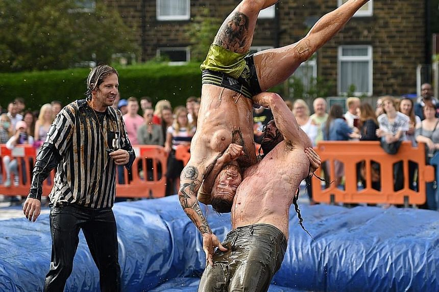 Competitors facing off in the 10th annual World Gravy Wrestling Championships held at a pub in Lancashire in north-west England on Monday. The contestants take part in fancy dress and wrestle in a pool of Lancashire Gravy for two minutes while being