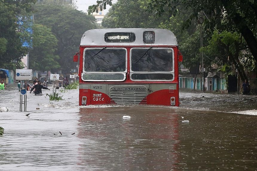 A bus moving through a water-logged road in Mumbai yesterday. Dozens of flights and train services were cancelled as India's meteorological department warned that the relentless downpour would continue for 24 hours.