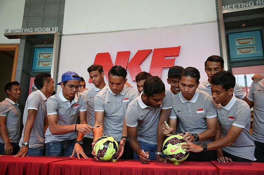 National football captain Shahril Ishak (second from right), vice-captain Hariss Harun (third from right) and the rest of the team signing two footballs, which will be auctioned off later to raise funds for the National Kidney Foundation (NKF). The L