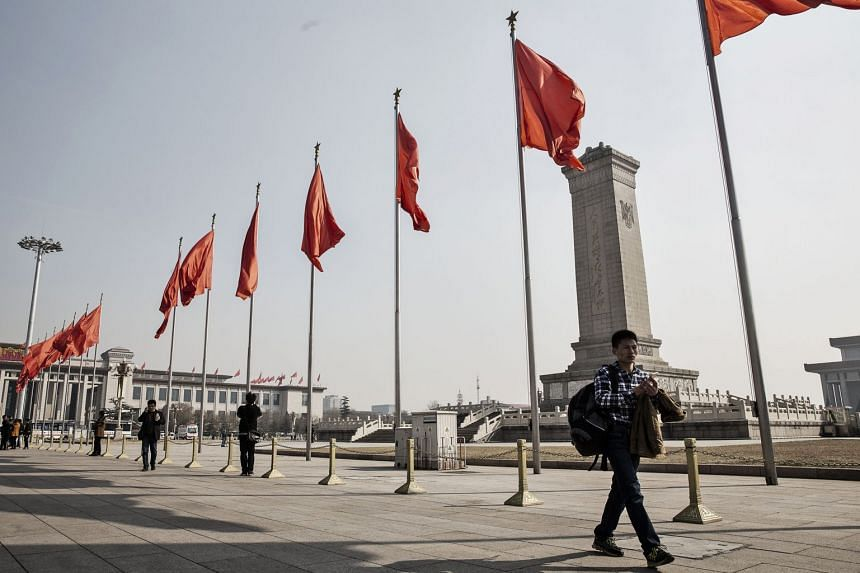 Pedestrians walk past red flags at Tiananmen Square in Beijing, China.
