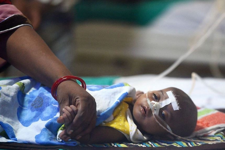An Indian woman holding her child's hand at the encephalitis ward of the Baba Raghav Das Hospital in Gorakhpur, in the northern Indian state of Uttar Pradesh.
