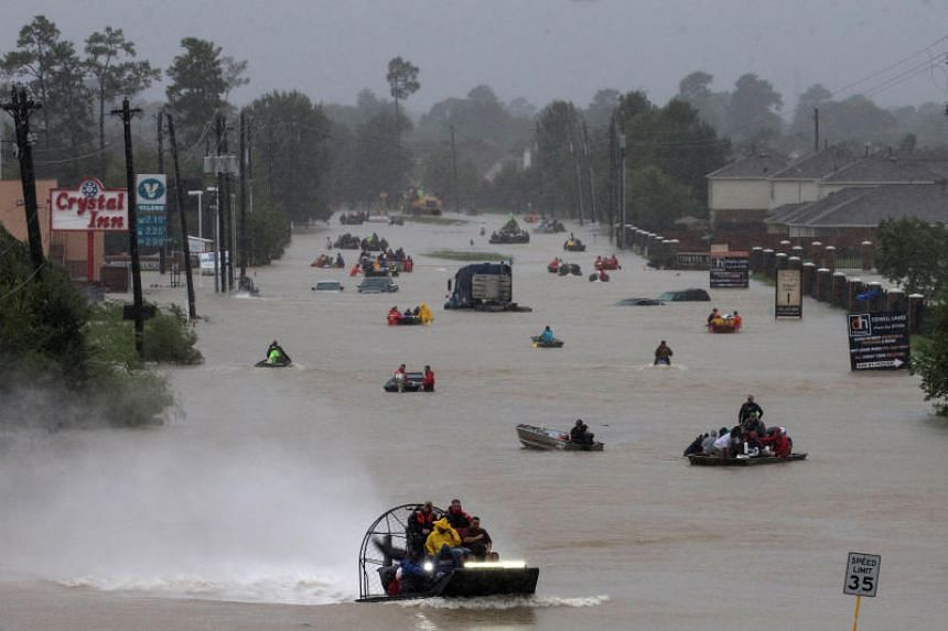 Residents use boats to evacuate flood waters from Tropical Storm Harvey along Tidwell Road in east Houston, Texas, on August 28, 2017.