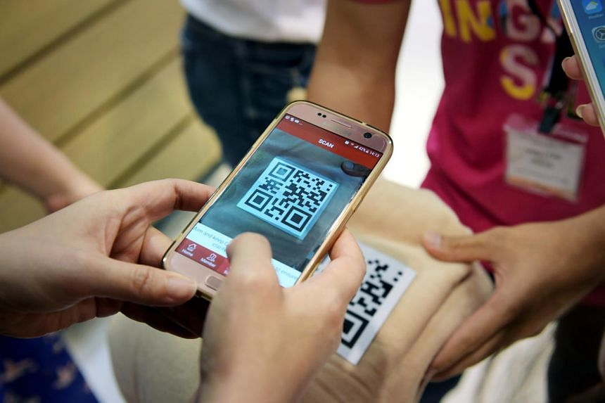 A shopper downloads the app to scan the QR code at the Robinsons store at Raffles City.