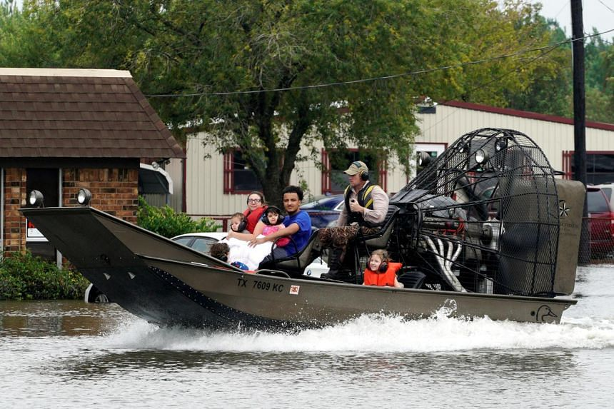 A family is rescued from flood waters from Hurricane Harvey on an air boat in Dickenson, Texas on Aug 27, 2017.