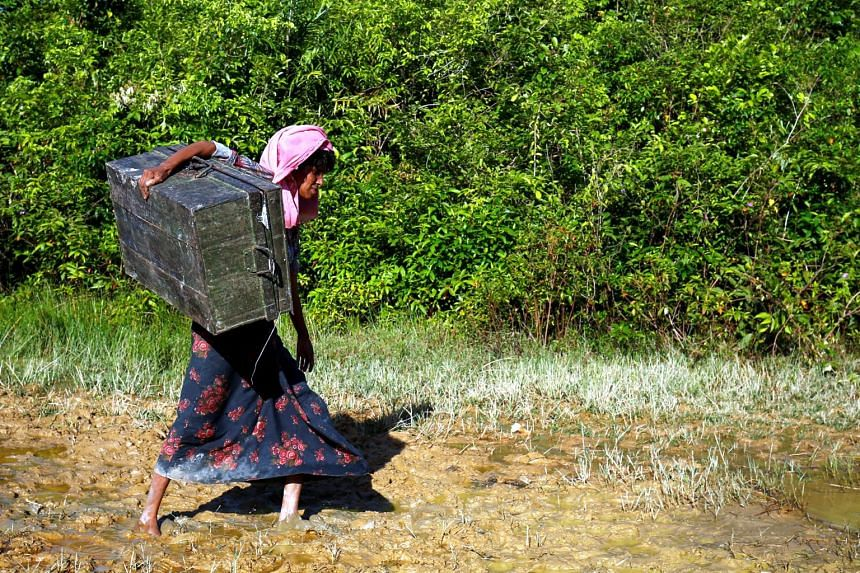 A Rohingya woman carries her belongings after crossing the Bangladesh-Myanmar border fence.
