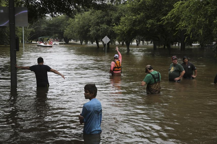 Volunteer and rescue officials wait to help residents to safety after they had to be rescued by boats from their homes after the area flooded in Houston.