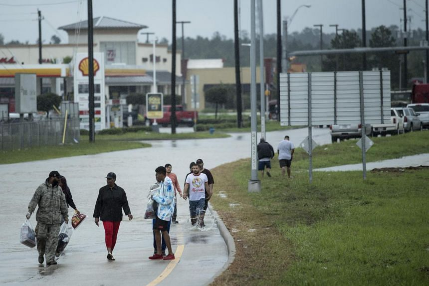 People walk from a flooded area during the aftermath of Hurricane Harvey.