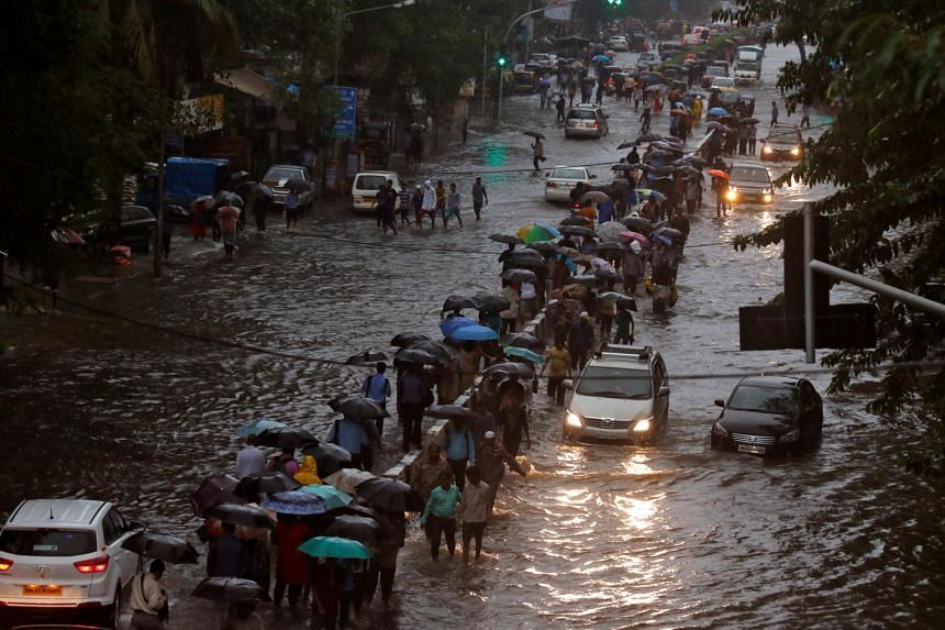 Commuters walk through water-logged roads after rains in Mumbai, on Aug 29, 2017.