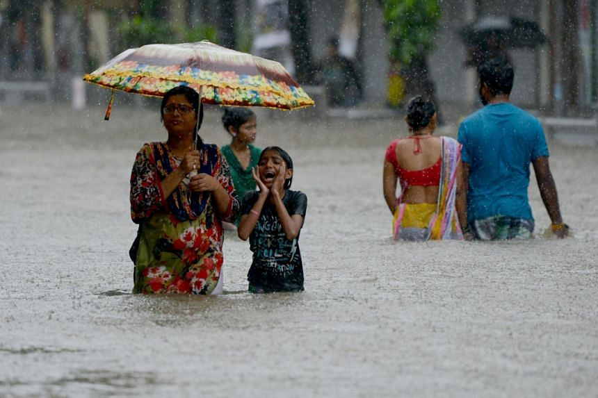 Indians wade through a flooded street during heavy rain showers in Mumbai, on Aug 29, 2017.
