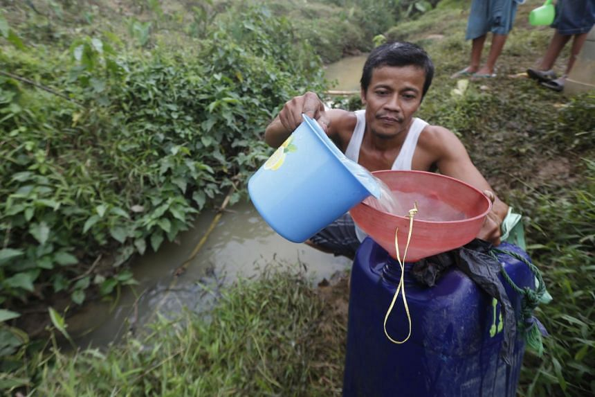 A resident fills a tank with dirty water from a river at Galih Manah village in Cibarusah, West Java, Indonesia.
