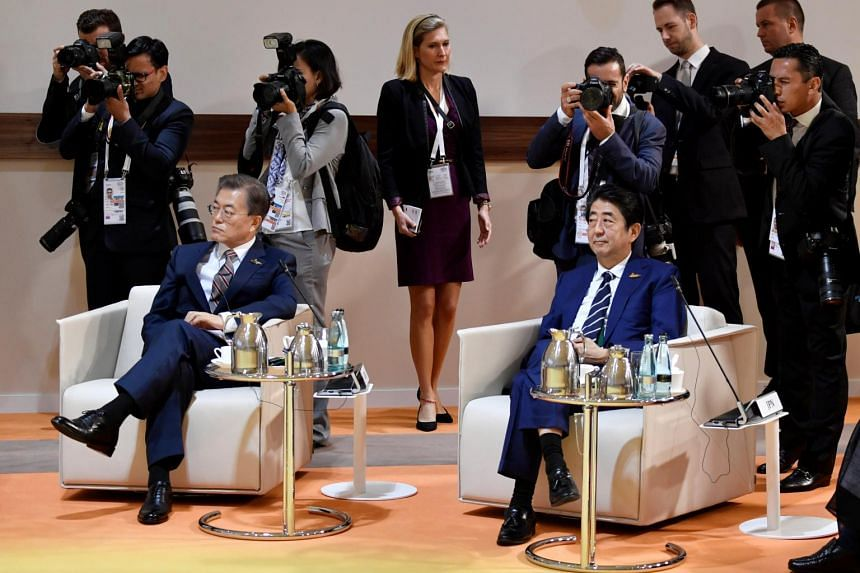 """South Korea's President Moon Jae In (left) and Japan's Prime Minister Shinzo Abe sit at the start at the start of the """"retreat meeting"""" on the first day of the G20 summit in Hamburg, Germany, on July 7, 2017."""