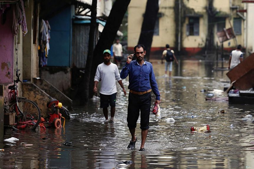 People walk through a partially flooded street in Mumbai.